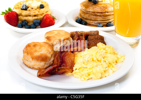 Breakfast plate with scrambled eggs, bacon, and buttermilk biscuits.  Waffles, pancakes, and orange juice in background. - Stock Photo