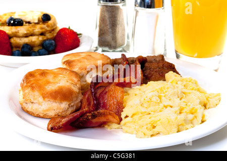 Big country breakfast with scrambled eggs, bacon, buttermilk biscuits, waffles, fruit, and orange juice. - Stock Photo