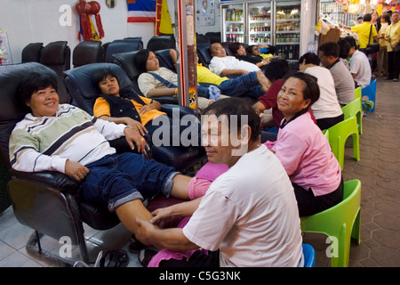 A group of tourists are sitting in large reclining chairs receiving foot massage therapy in Northern Thailand. - Stock Photo