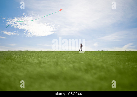 A man flying a red kite - Stock Photo