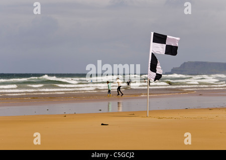 Black and white chequered surfers flag warning swimmers that surfers and kayaks are in the area - Stock Photo
