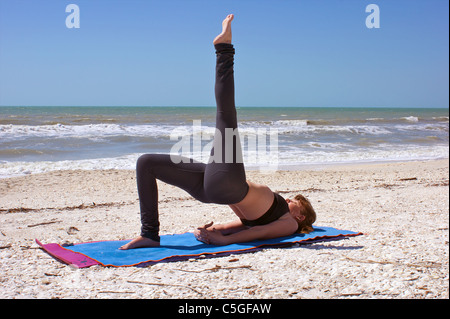an athletic brown haired woman is doing yoga exercise one leg bridge pose on an empty beach - Stock Photo