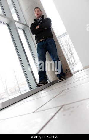 A young man standing by some large windows from a low angle perspective. - Stock Photo