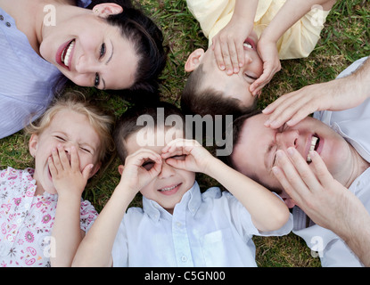 Happy family lying in the ground, aerial view - Stock Photo