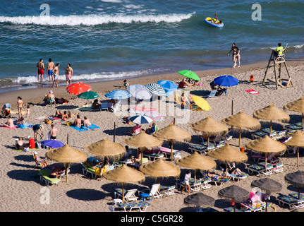 HOLIDAYMAKERS ENJOYING THE SEA AND SAND UNDER UMBRELLAS ON THE BEACH IN FUENGIROLA COSTA DEL SOL WATCHED BY A LIFEGUARD - Stock Photo