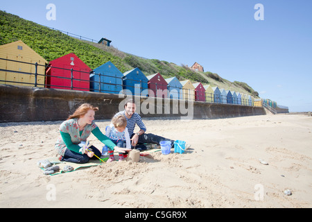 Young family building sand castles on the beach in front of beach huts at Mundesley on the Norfolk Coast - Stock Photo
