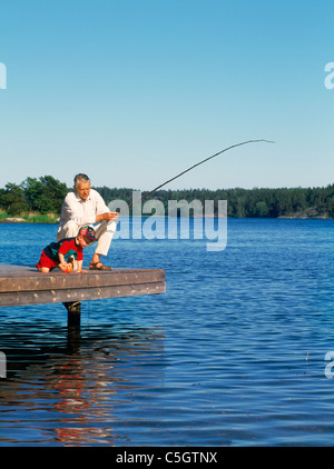 Grandfather fishing with grandchild off wooden dock along Baltic Sea shoreline during Swedish summer - Stock Photo