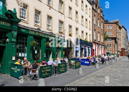 People sitting outside a pub (The White Hart Inn) on Grassmarket in the Old Town, Edinburgh, Scotland, UK - Stock Photo