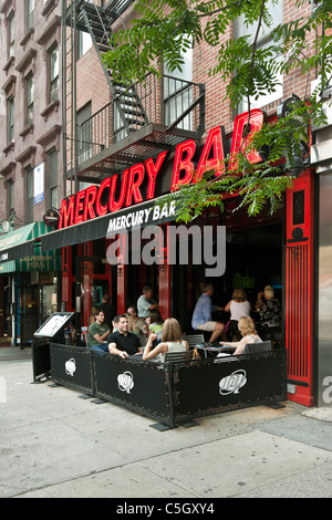 patrons enjoying drinks inside at bar & at outdoor tables seating Mercury Bar in Hells Kitchen neighborhood New - Stock Photo