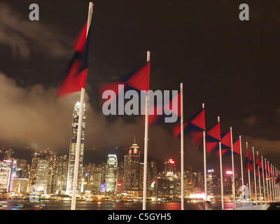 View looking up at a line of colourful flags flying in the wind with Hong Kong Island  in the background at night - Stock Photo