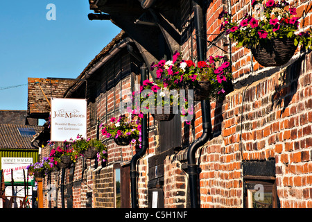 Pretty Hanging baskets which decorate shops in 'Monks Granary' along Standard Quay in Faversham Kent - Stock Photo