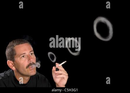 A man smoking a cigarette blows smoke rings against a black backdrop. - Stock Photo