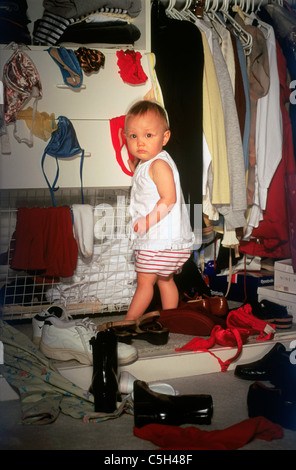 Baby in parent's bedroom closet creating mixed mess of shoes and clothing with a guilty look on face - Stock Photo