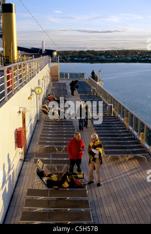passengers on Costa Atlantica talk and watch sunset on deck - Stock Photo