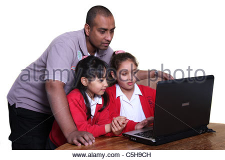 A father helping his daughters with their homework. - Stock Photo