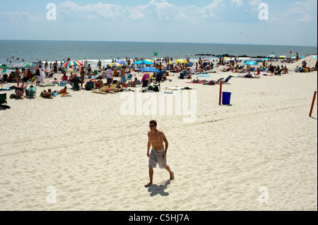 Beachgoers take advantage of the warm summer sun at the beach at the City of Long Beach, Long Island, New York - Stock Photo