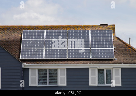 Twelve photovoltaic solar panels on an energy efficient eco home house roof residential domestic property. West - Stock Photo