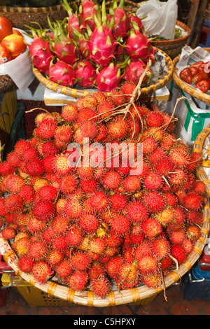 Rambutan, lychee like fruit for sale in Hom Market, a typical crowded market in the Old Quarter of Hanoi - Stock Photo