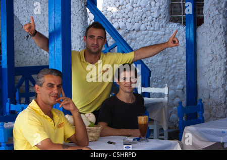 3 greek men greeting the viewer in a restaurant in Thera - Stock Photo