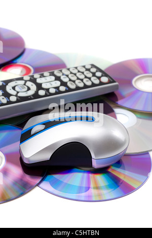 TV remote control and computer mouse on a pile of scattered dvd disks isolated over white. - Stock Photo