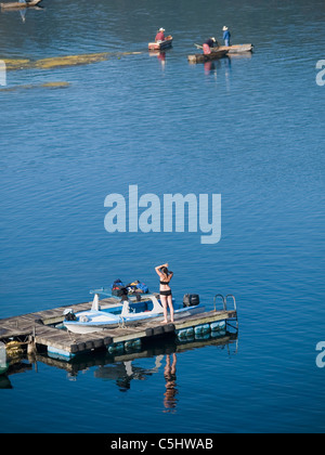 Tourits in bathing suits contrast with fully dressed local people on Lake Atitlan in  Santiago Atitlan, in the highlands - Stock Photo