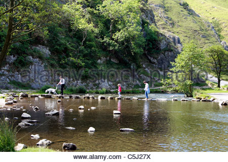 Family crossing the river Dove on famous stepping stones at Dovedale in Peak District National Park  Staffordshire - Stock Photo
