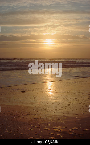 Low winter sun glows through thin cloud over the Moray Firth near Golspie, northern Scotland, UK. - Stock Photo