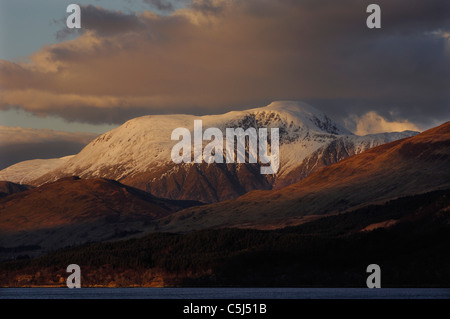 The warmly-lit, snow-covered summit of Ben Nevis, Scotland's highest mountain, rises above dark foothills, seen - Stock Photo