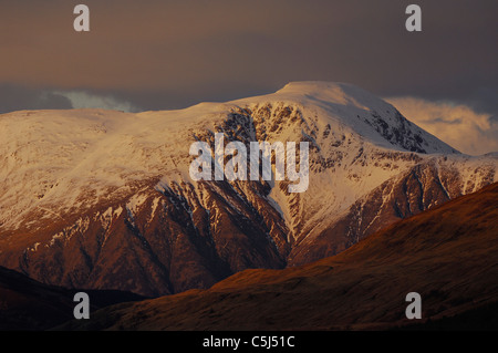 Telephoto shot of the warmly-lit, snow-covered summit of Ben Nevis, Scotland's highest mountain, rises above dark - Stock Photo