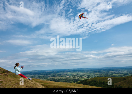 Girl flying kite at British Camp Iron Age hill fort in the Malvern Hills. - Stock Photo