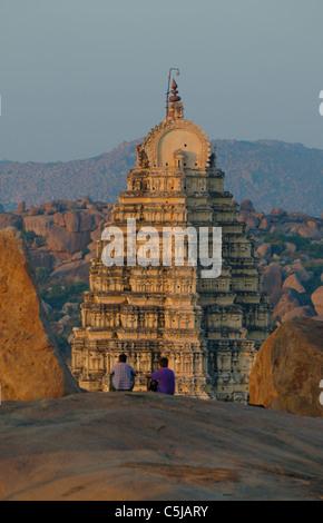 Tourists enjoying the view from Hemakuta Hill onto Virupaksha Temple at sunset in Hampi, Karnataka, India. - Stock Photo