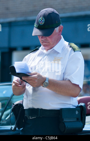 A Traffic warden writing a ticket for an illegally parked car. Stratford on Avon. UK - Stock Photo