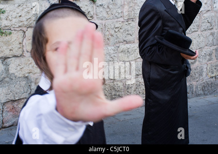An ultra-Orthodox Jew tries to prevent his photograph being taken during riots to close The Prophets' Road (HaNeviim). - Stock Photo
