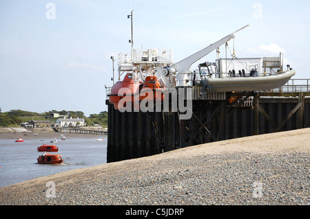 The boat launching station at Fleetwood with boats secured on davits and cables and others in the water - Stock Photo