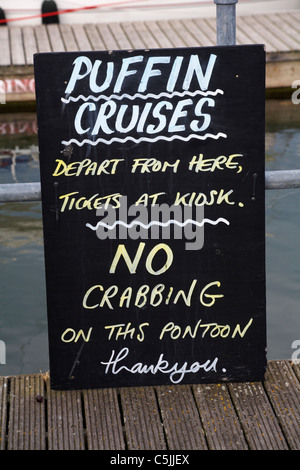 Puffin cruises advertised on blackboard at Lymington Harbour in June - Stock Photo