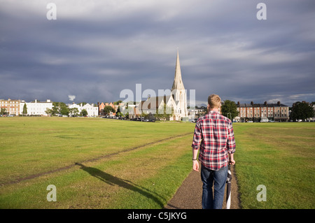 A young man walking across heath to village with All Saints parish church in evening sunlight. Blackheath, London, - Stock Photo