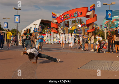 A street performer busking outside the entrance to Disney Village at Disneyland Paris in France - Stock Photo