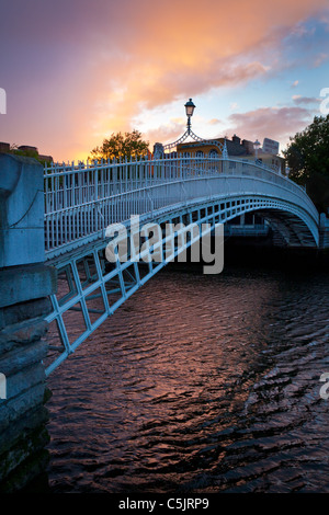 Liffey, or Ha'Penny, Bridge in Dublin, Ireland at dusk - Stock Photo
