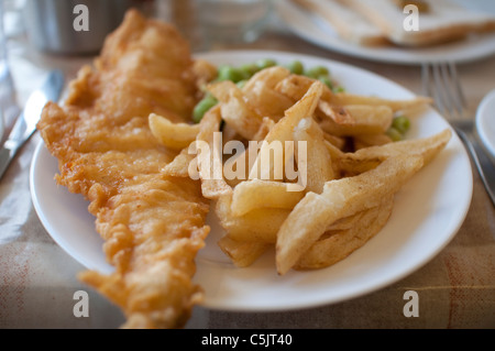 Fish and Chips served with mushy peas on a plate in England. - Stock Photo