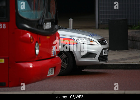 The nose of a parked police car next to the front of a parked double decker bus in London - Stock Photo