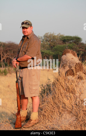 A guide carries a rifle on a morning nature trek in Hwange National Park, Zimbabwe. - Stock Photo