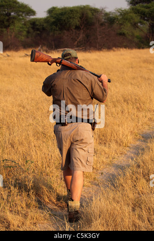 A guide carries a rifle on his shoulder on an early morning nature trek in Hwange National Park, Zimbabwe. - Stock Photo