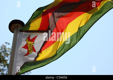 The Zimbabwean national flag flies from a flagpole in Zimbabwe. - Stock Photo