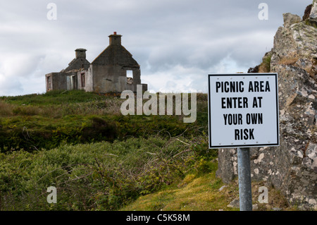 A genuine welcoming sign for a picnic area warns that it is to be used at your own risk. - Stock Photo