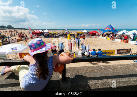 A young girl watching the Margate Masters Beach Volleyball championships on Margate beach. - Stock Photo