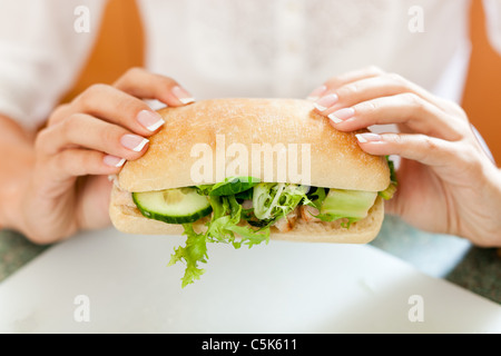 Blonde girl eating healthy sandwich - Stock Photo