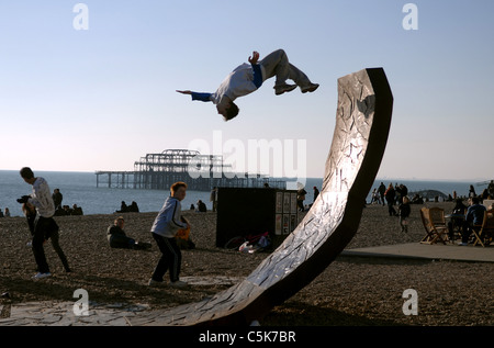 A youngster performs a spectacular back flip on one of the Passacaglia sculpture on Brighton beach