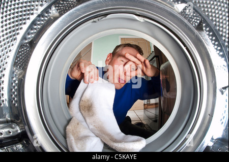 man holding nose putting smelly dirty socks into washing machine - Stock Photo