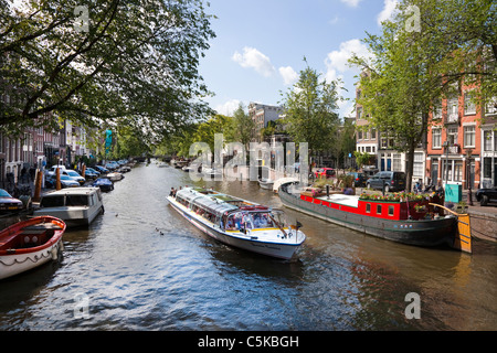 Tourist canal boat sailing along a canal in Amsterdam, Netherlands - Stock Photo