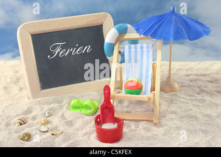 School board and toys on a sandy beach - Stock Photo